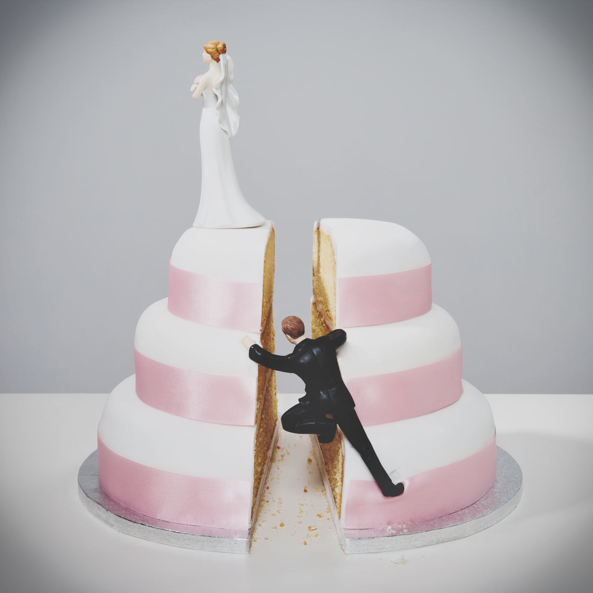Food photographer - a concept image of male figure climbing up side of wedding cake