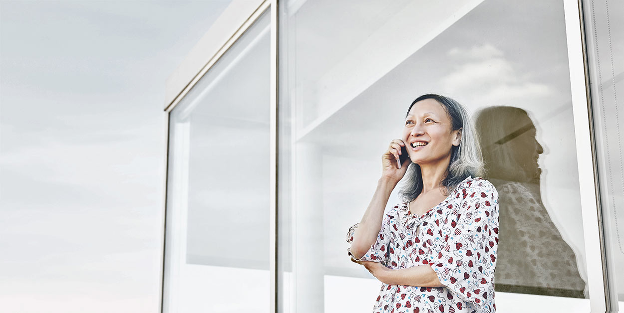 Corporate Photographer - woman standing outside office using mobile phone smiling .  Business photography for Charity
