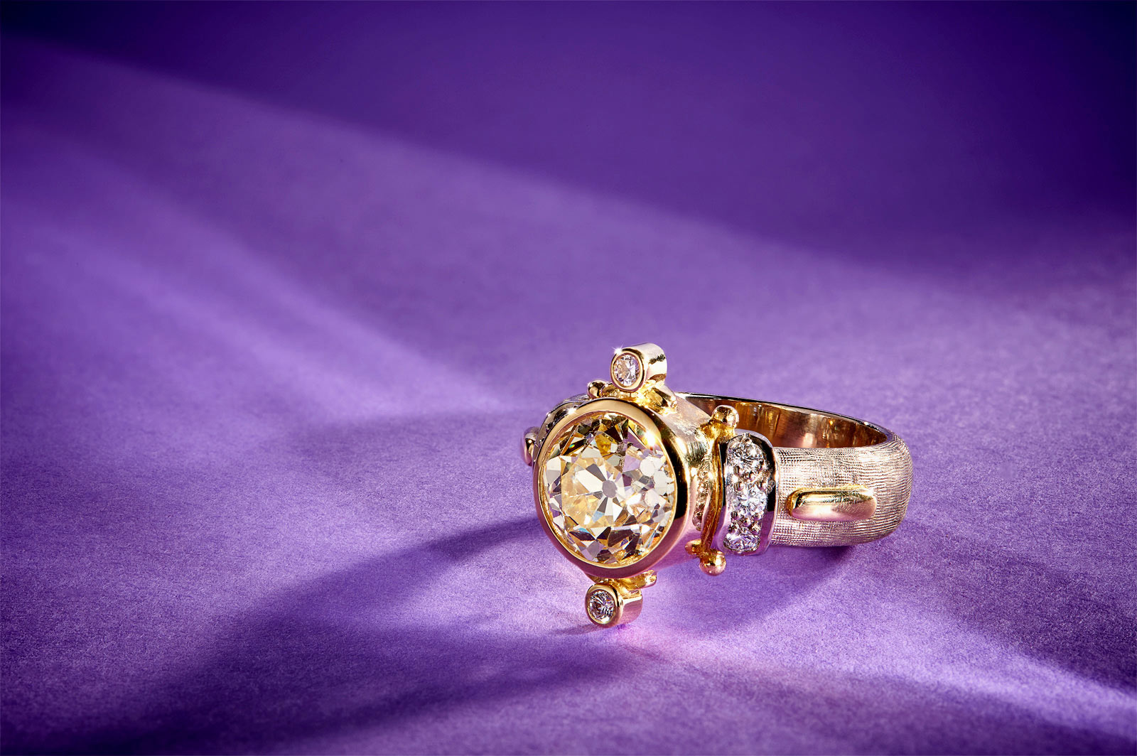 Jewelry  photography - gold ring with large stone on purple background