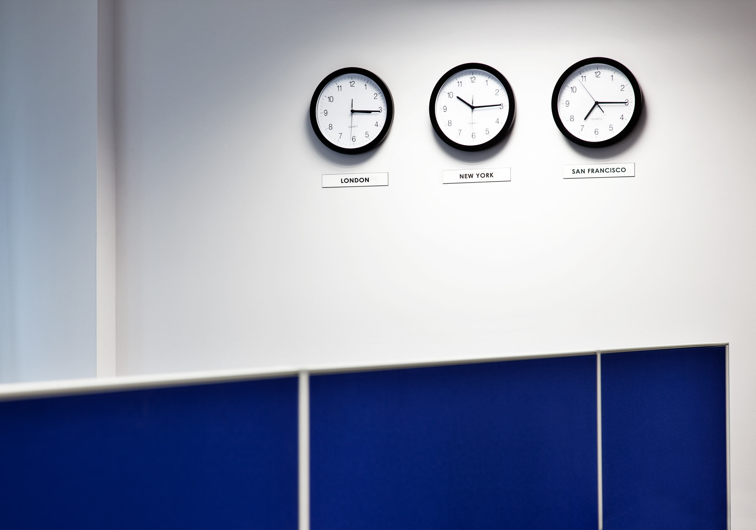 Location photography - 3 clocks showing times in various zones on white wall with blue office divider