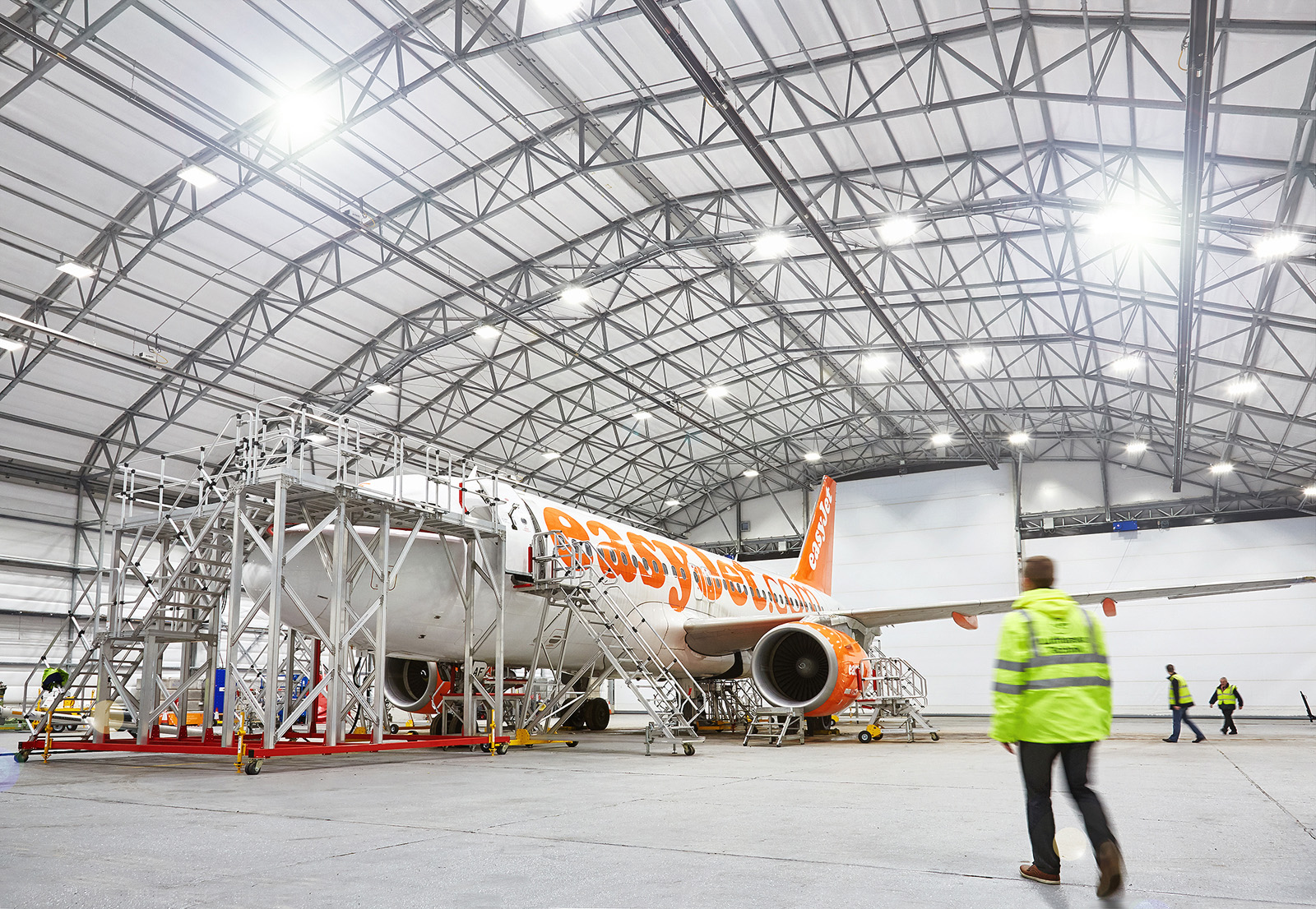 London photography - gatwick airport - easy jet plane in hanger with technician walking to towards plane.  Location image for engineering company  based in Surrey