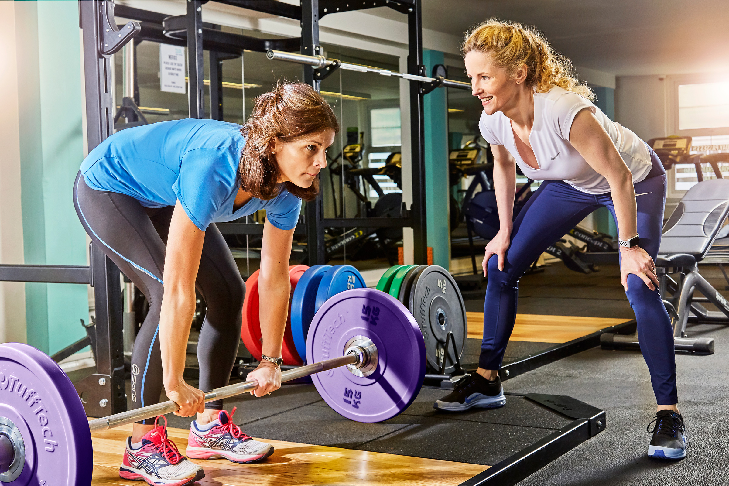 Location photography surrey uk - fitness coach training woman using weights in the gym.  Local business photography, Sussex